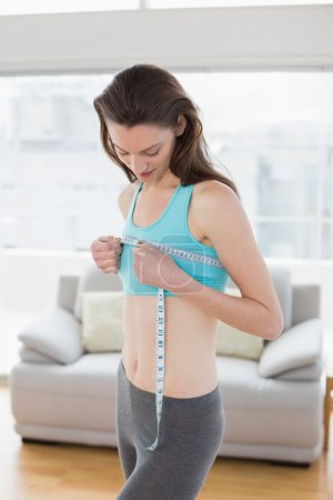 Toned woman measuring chest in fitness studio
