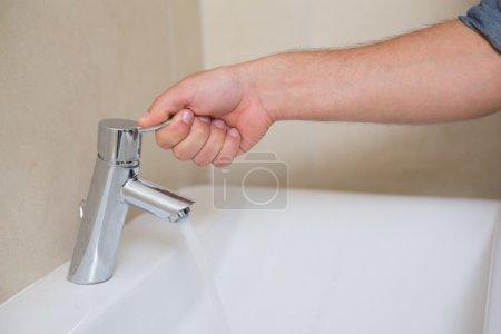 Photo pour Extrême bouchent de main de plombier, ouvrir un robinet d'eau à la salle de bain - image libre de droit