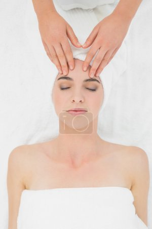 Hands massaging a beautiful woman's forehead at beauty spa