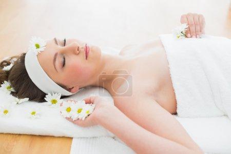 Photo pour Frais généraux d'une belle jeune femme avec les yeux fermés couché sur la table de massage dans un salon de beauté - image libre de droit