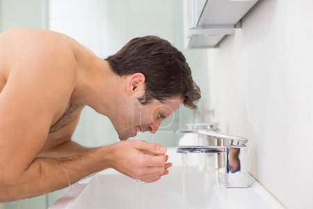Side view of shirtless man washing face in bathroom