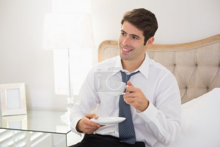 Smiling well dressed man with a cup of tea in bed