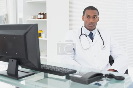 Serious male doctor sitting with computer at medical office