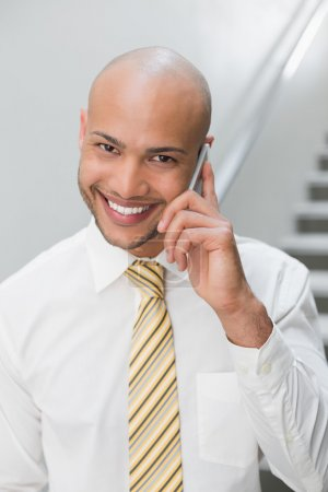 Smiling businessman using cellphone in office