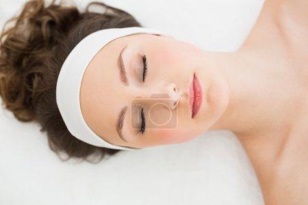 Photo pour Jeune brune allongée sur une table de massage les yeux fermés dans un salon de beauté - image libre de droit