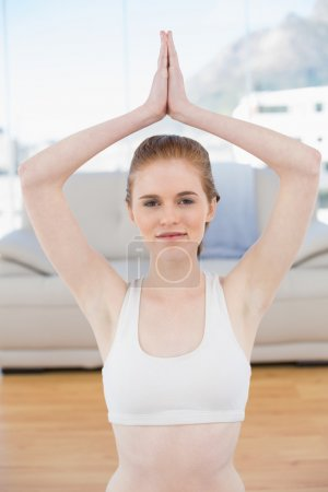 Woman with joined hands over head at fitness studio