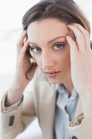 Close up portrait of businesswoman suffering from headache