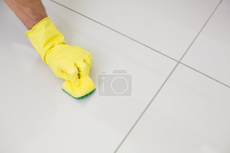 Yellow gloved hand with sponge cleaning the floor