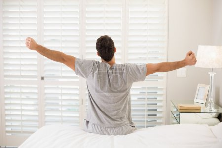 Rear view of man stretching his arms in bed