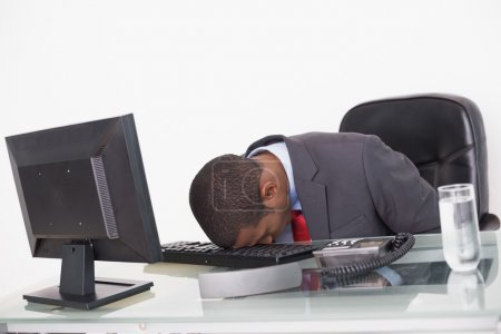 Photo for Young Afro businessman resting head on keyboard in the office - Royalty Free Image