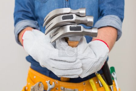 Photo for Close up mid section of a handyman holding hammers with toolbelt around waist - Royalty Free Image