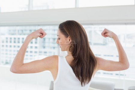Fit brown haired woman flexing muscles in fitness studio
