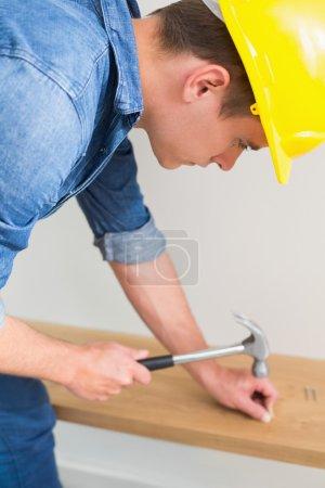 Handyman hammering nail in wooden bench