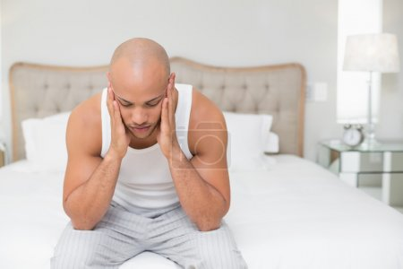 Bald man suffering from headache in bed