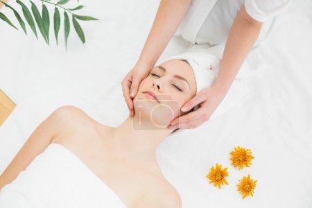 Hands massaging a beautiful woman's face