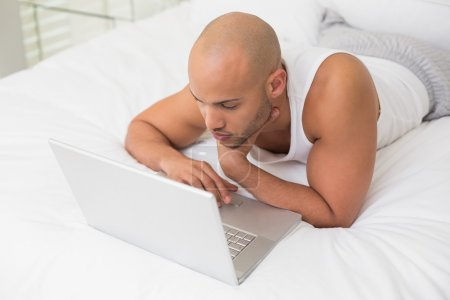 Serious casual bald man using laptop in bed