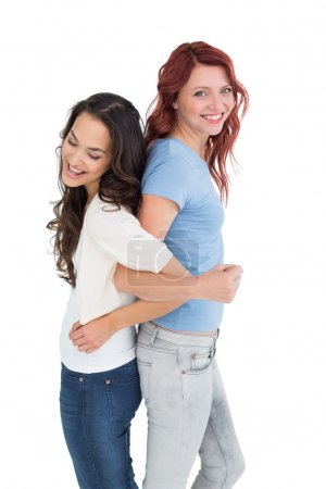Young women standing back to back with interlocked hands