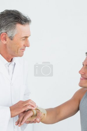 Male doctor examining a patients hand