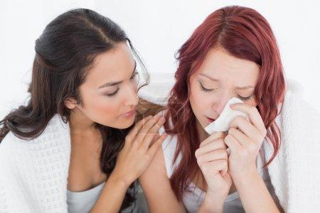 Photo pour Jeune femme consoler une amie pleure tout en étant assis sur le lit à la maison - image libre de droit