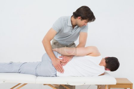 Male physiotherapist examining patient