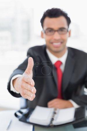 Blurred businessman offering a handshake at desk