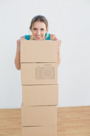 Smiling woman with a stack of boxes in new house