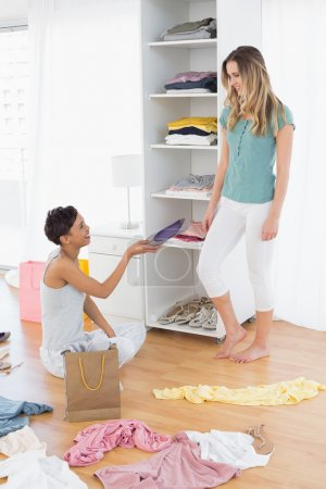 Happy young women arranging clothes in shelf