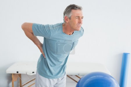 Photo for Mature man with lower back pain standing in the gym at hospital - Royalty Free Image
