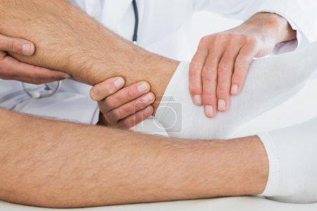 Close-up of hands examining patients knee