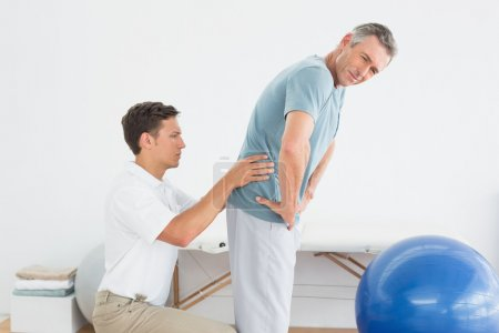Therapist massaging mans lower back in gym hospital