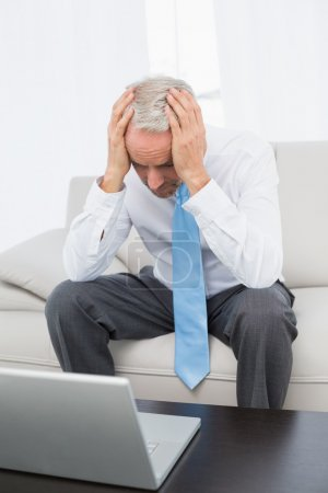 Photo for Worried mature businessman with head in hands in front of laptop in the living room at home - Royalty Free Image