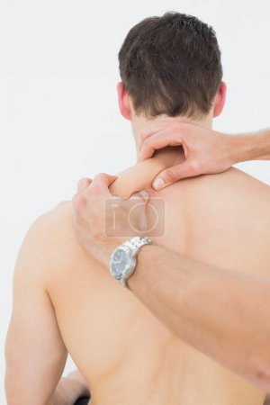Photo for Man being massaged by a physiotherapist over white background - Royalty Free Image