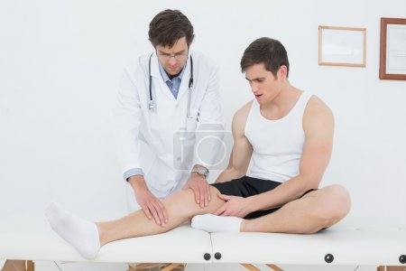 Full length of a young man getting his knee examined