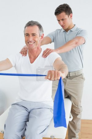 Photo for Male therapist massaging mans shoulder in the gym at hospital - Royalty Free Image