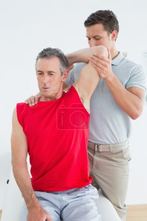 Male physiotherapist stretching a mature mans arm