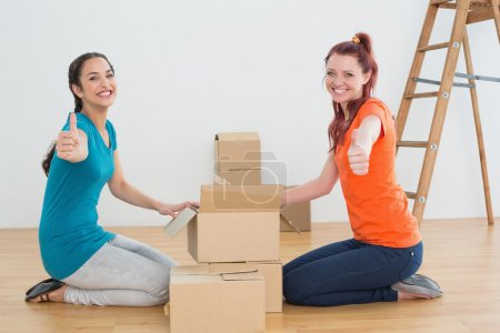 Female friends gesturing thumbs up with boxes in a new house