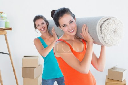 Friends carrying rolled rug after moving in a house