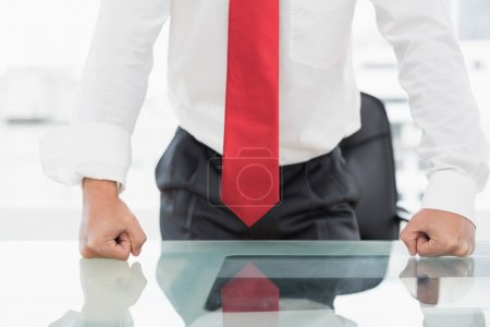 Mid section of a businessman with clenched fists on desk