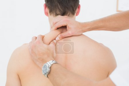 Rear view of a man being massaged by a physiotherapist