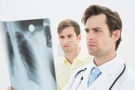 Concentrated doctor and patient examining lungs x-ray