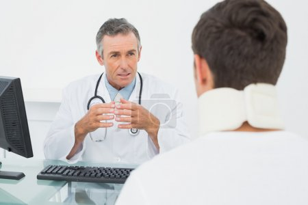 Doctor in conversation with patient in office