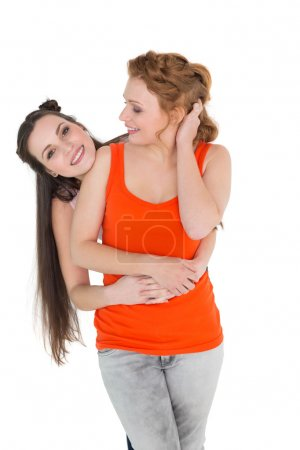 Cheerful young female embracing her friend