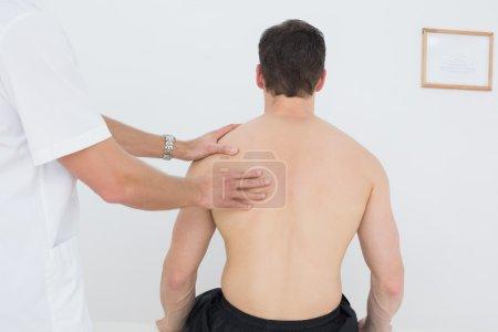 Photo pour Homme massé par un physiothérapeute sur fond blanc - image libre de droit