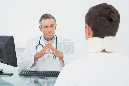 Doctor listening to patient with concentration in office