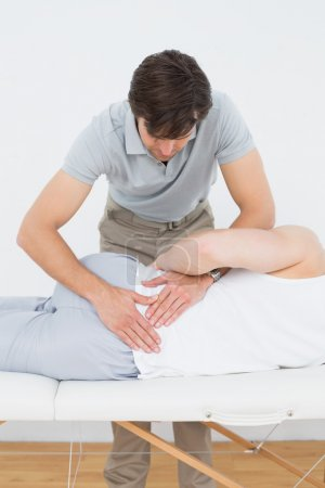 Male physiotherapist examining mans back