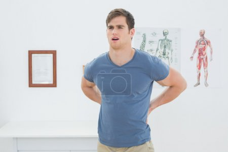 Handsome young man with back pain standing in office