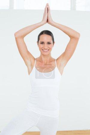 Photo pour Portrait d'une jeune femme sportive avec les mains jointes au-dessus de la tête dans un studio de remise en forme - image libre de droit