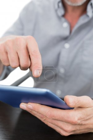 Mid section of a businessman using digital tablet at table