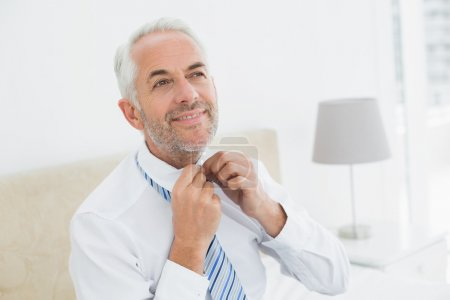 Mature businessman adjusting neck tie at home