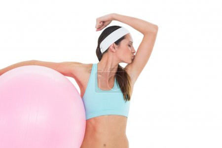 Fit woman kissing muscles with fitness ball